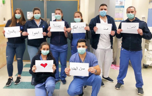 """Medical staff holding signs that say """"We are at Work for You"""" in Arabic"""